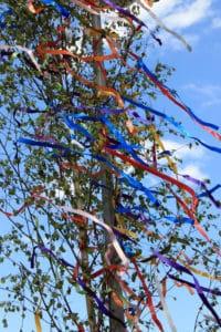 Maibaum mit Satinbändern geschmückt